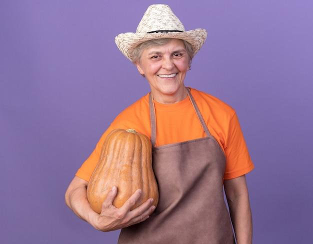 Uśmiechnięta starsza kobieta ogrodniczka w kapeluszu ogrodniczym trzymająca dynię