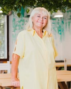 Uśmiechnięta starsza kobieta opiera na stole