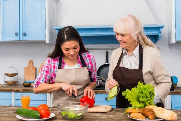 Uśmiechnięta starsza kobieta patrzeje córki tnącego warzywa w kuchni