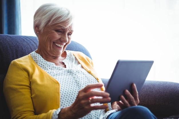 Uśmiechnięta starsza kobieta patrzeje i śmia się przy jej cyfrową pastylką