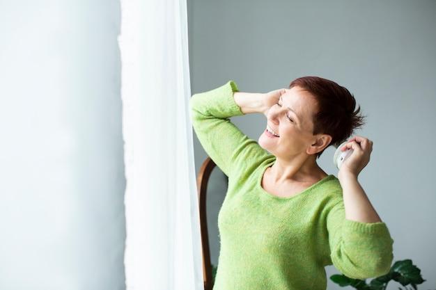 Uśmiechnięta starsza kobieta patrzeje na okno