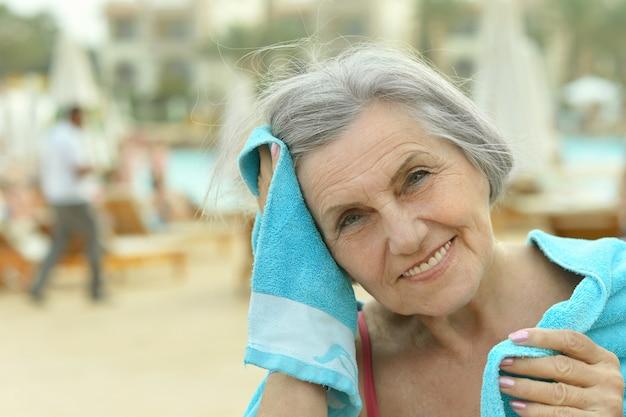 Uśmiechnięta starsza kobieta przy basenie z ręcznikiem
