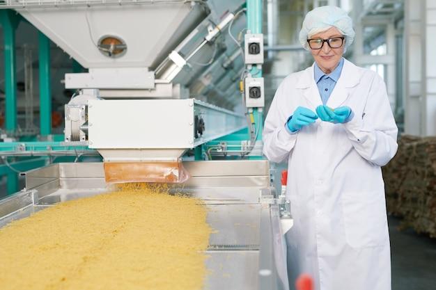 Uśmiechnięta starsza kobieta przy linią produkcyjną