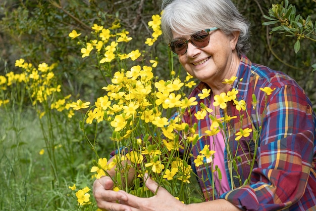 Uśmiechnięta starsza kobieta przytula grupę żółtych kwiatów w pełnym rozkwicie w lesie.