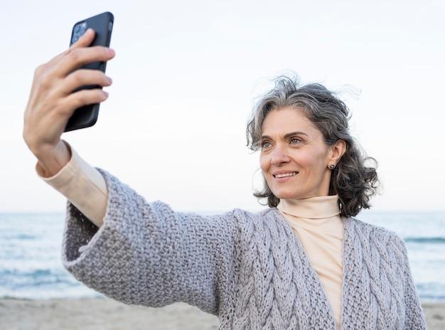 Uśmiechnięta starsza kobieta robi selfie przy plaży