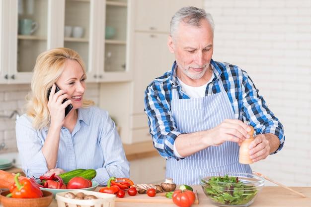 Uśmiechnięta starsza kobieta rozmawia przez telefon komórkowy i jej mąż przygotowuje sałatkę w kuchni