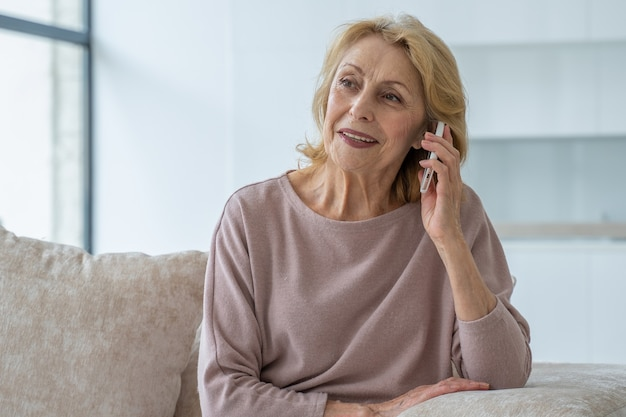 Uśmiechnięta starsza kobieta rozmawiająca przez telefon komórkowy w domu, relaksująca się na kanapie w salonie