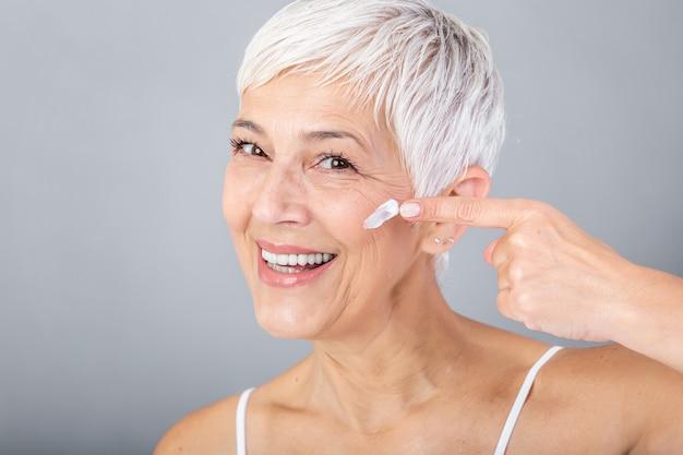 Uśmiechnięta starsza kobieta stosuje przeciw starzeniu się balsam do usuwania cieni pod oczami. starsza kobieta za pomocą kremu kosmetycznego, aby ukryć zmarszczki. pani za pomocą kremu nawilżającego na dzień, aby przeciwdziałać starzeniu się skóry.