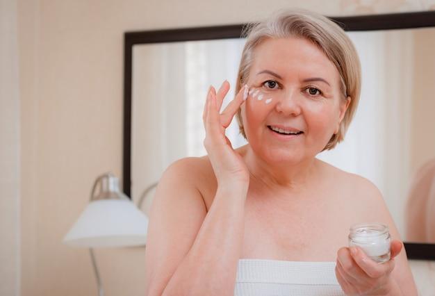 Uśmiechnięta starsza kobieta stosuje przeciw starzeniu się balsam do usuwania cieni pod oczami.