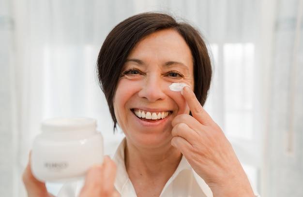 Uśmiechnięta starsza kobieta stosuje starzenie się twarzy śmietankę w domu. szczęśliwa dojrzała kobieta używa dnia moisturizer