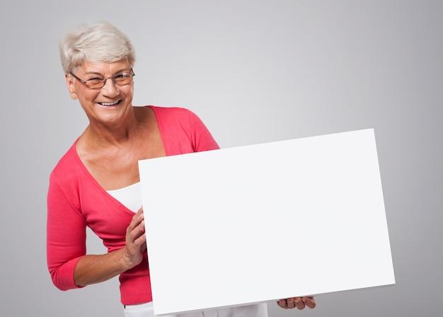 Uśmiechnięta starsza kobieta trzyma białą tablicę