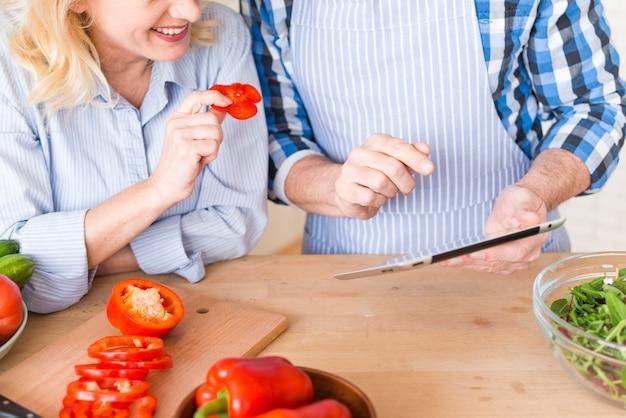 Uśmiechnięta starsza kobieta trzyma dzwonkowego pieprzu w ręce patrzeje cyfrową pastylkę