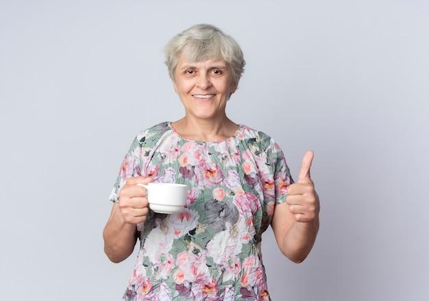 Uśmiechnięta starsza kobieta trzyma kubek i kciuki na białym tle na białej ścianie