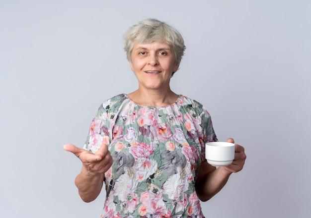 Uśmiechnięta starsza kobieta trzyma kubek i punkty na białym tle na białej ścianie