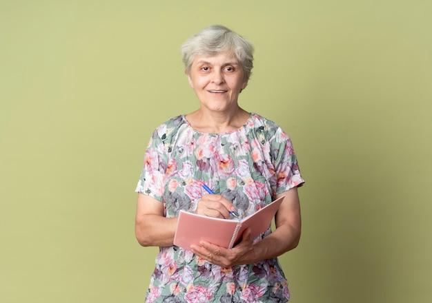 Uśmiechnięta starsza kobieta trzyma pióro i notatnik, patrząc na białym tle na oliwkowej ścianie