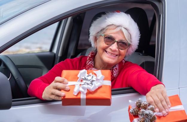 Uśmiechnięta starsza kobieta ubrana na czerwono wychyla się z okna samochodu w świątecznym kapeluszu i trzyma świąteczne prezenty