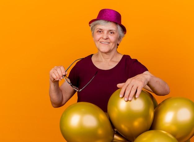 Uśmiechnięta starsza kobieta ubrana w imprezowy kapelusz stoi z balonami z helem, trzymając okulary optyczne na białym tle na pomarańczowej ścianie