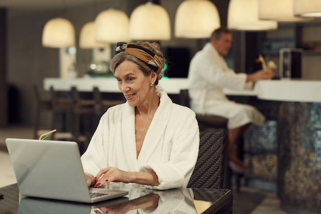 Uśmiechnięta starsza kobieta używa laptop w zdroju
