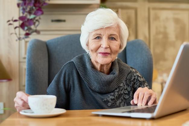 Uśmiechnięta starsza kobieta używa laptop