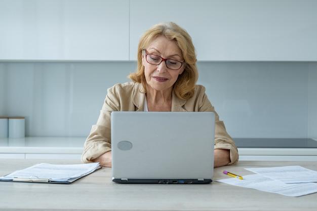 Uśmiechnięta starsza kobieta używająca laptopa i patrząca w kamerę biznesowa kobieta używa swojego laptopa