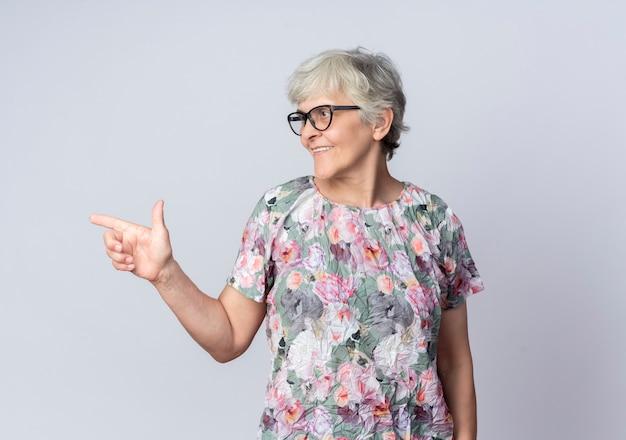 Uśmiechnięta starsza kobieta w okularach optycznych wygląda i wskazuje na bok na białym tle na białej ścianie