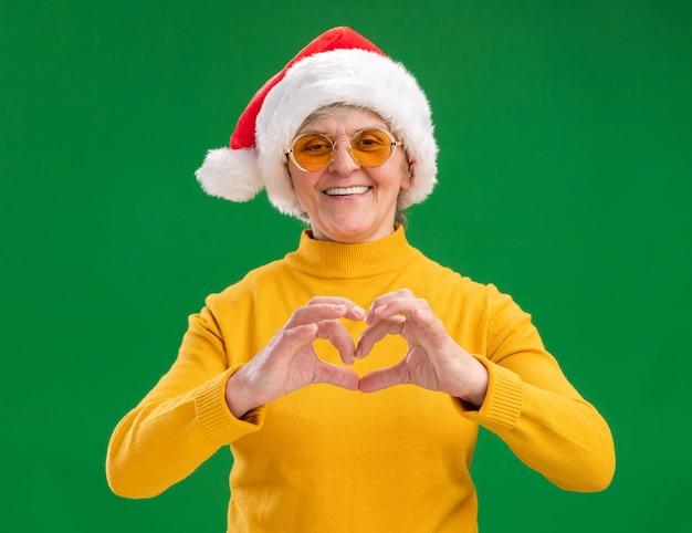 Uśmiechnięta starsza kobieta w okularach przeciwsłonecznych z kapeluszem santa gestykuluje znak serca na białym tle na zielonym tle z miejsca na kopię