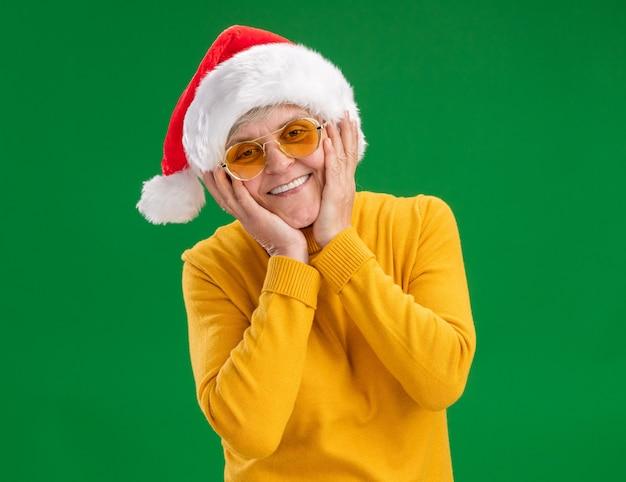 Uśmiechnięta starsza kobieta w okularach przeciwsłonecznych z kapeluszem santa kładzie ręce na twarzy na białym tle na zielonym tle z miejsca na kopię