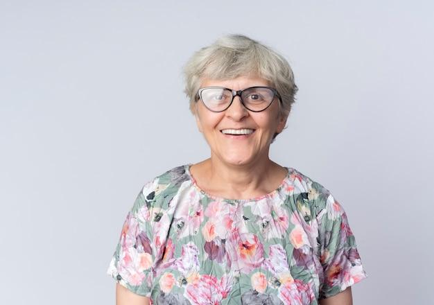 Uśmiechnięta starsza kobieta w optycznych okularach stoi na białym tle na białej ścianie