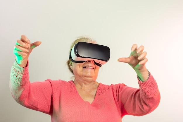 Uśmiechnięta starsza kobieta w różowym swetrze z okularami wirtualnej rzeczywistości i uniesionymi rękami patrząc prosto przed siebie oświetlona czerwonymi i zielonymi światłami na jasnym tle