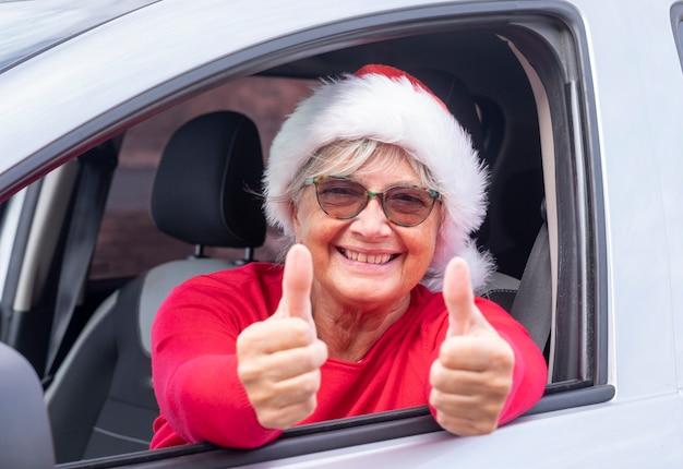 Uśmiechnięta starsza kobieta w samochodzie w świątecznym kapeluszu uśmiechająca się z kciukami do góry przez okno w oczekiwaniu na nadchodzące wakacje - wydarzenie. pojęcie szczęścia
