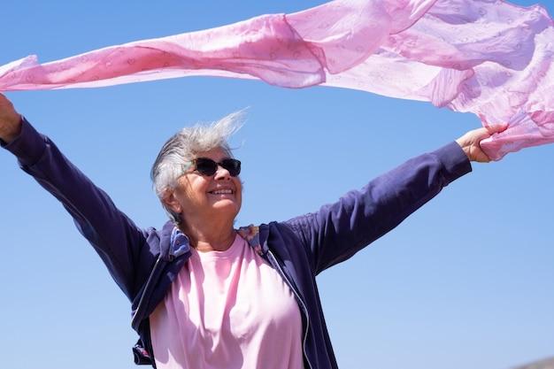 Uśmiechnięta starsza kobieta w wietrzny dzień opuszcza jej szalik macha. osoba starsza cieszy się wakacjami i emeryturą