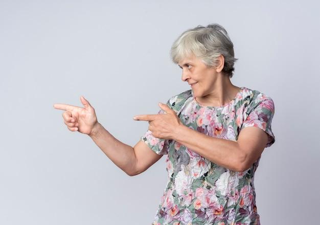Uśmiechnięta starsza kobieta wskazuje i patrzy na bok na białym tle na białej ścianie