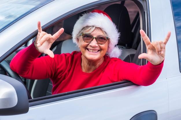 Uśmiechnięta starsza kobieta wychyla się z okna samochodu w świątecznym kapeluszu i uśmiecha się, gestykulując rękoma pozytywne znaki, czekając na nadchodzące wakacje - wydarzenie