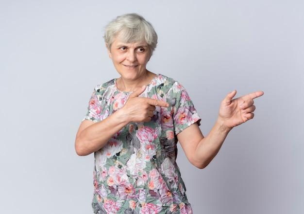 Uśmiechnięta starsza kobieta wygląda i wskazuje na bok dwiema rękami na białym tle na białej ścianie