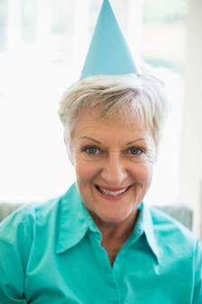 Uśmiechnięta starsza kobieta z partyjnym kapeluszem