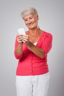 Uśmiechnięta starsza kobieta za pomocą smartfona