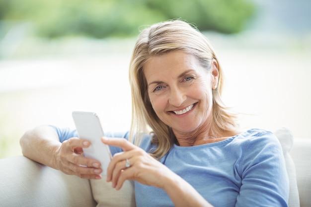 Uśmiechnięta starsza kobieta za pomocą telefonu komórkowego w salonie