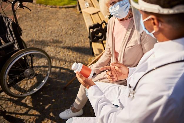 Uśmiechnięta starsza pani w masce patrząca na lekarza, gdy otrzymuje porady dotyczące jej leku
