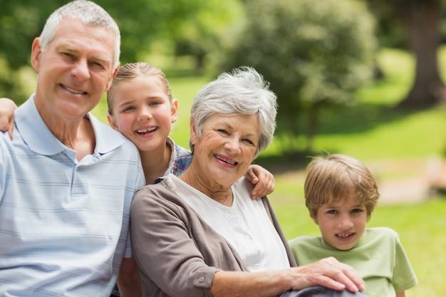 Uśmiechnięta starsza para i wnuki przy parkiem