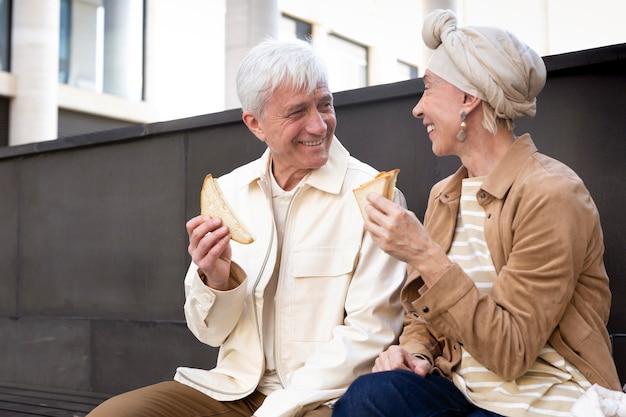Uśmiechnięta starsza para na zewnątrz przy kanapce razem?