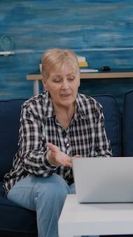 Uśmiechnięta starsza para patrząca na laptopa machającego podczas rozmowy wideo