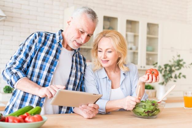 Uśmiechnięta starsza para patrzeje cyfrową pastylkę dla przygotowywać jedzenie w kuchni