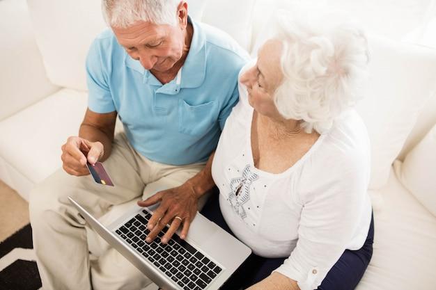 Uśmiechnięta starsza para używa laptop w domu