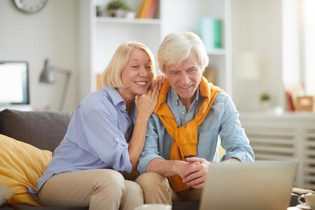 Uśmiechnięta starsza para używa laptop wpólnie