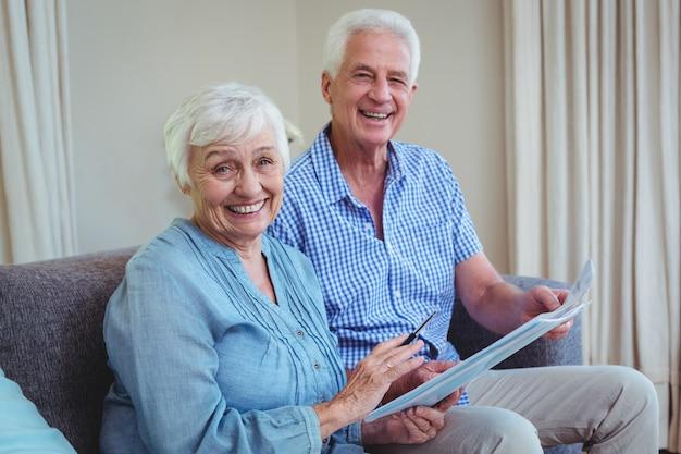 Uśmiechnięta starsza para z rachunkami