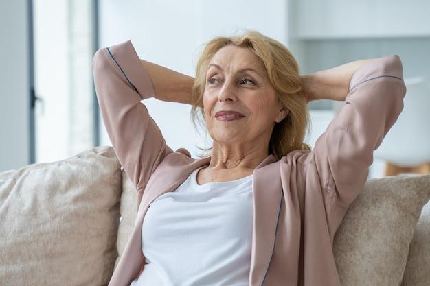 Uśmiechnięta starsza starsza pani odpoczywa na kanapie z rękami za głową relaksując się po długim czasie