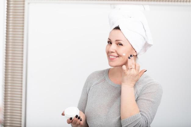 Uśmiechnięta starzejąca się kobieta stosuje starzenie się śmietankę
