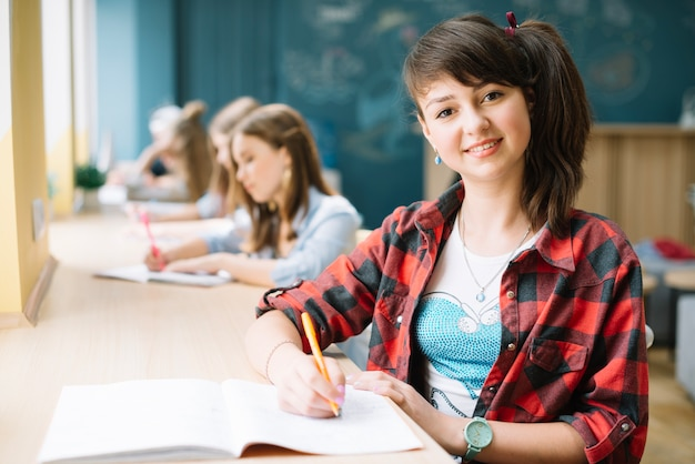 Uśmiechnięta student z notatnikiem w klasie