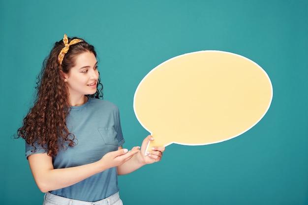 Uśmiechnięta studentka dziewczyna z kręconymi włosami trzymając transparent dymek podczas prezentacji na niebiesko