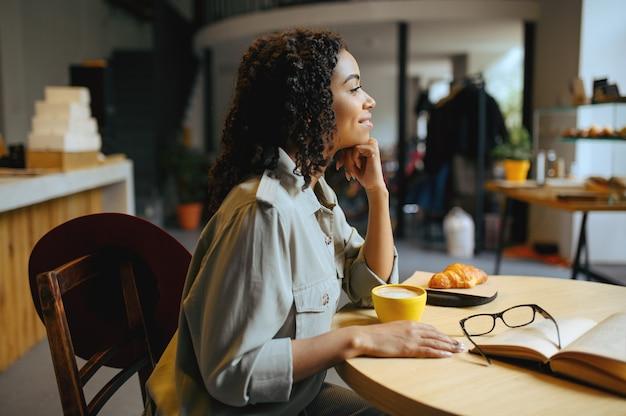 Uśmiechnięta studentka pije kawę z rogalikami w kawiarni